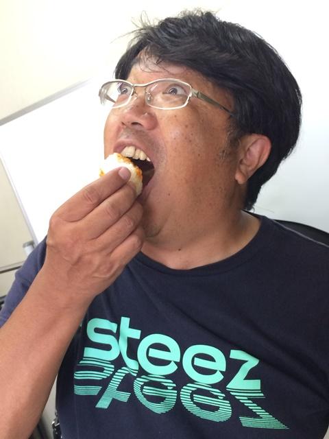 アサデス。取材レポート カメラマン雲丹醤油焼きおにぎりを食べるの図